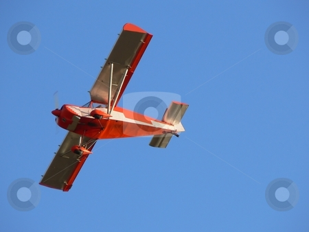 Red plane stock photo, Small red airplane flying over blue sky by Laurent Dambies