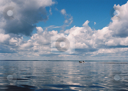 Surreal scene_boat on water stock photo, Still waters and cloud cover foretell impending events on Lake Winnibigoshish, Minnesota. by Bruce Peterson