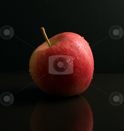Red Apple on black reflective surface stock photo, Red and Green Apple on black reflective surface by Mark Allchin