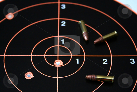 Target shoot 3 stock photo, Target with bullet hole on bullseye plus three .22 caliber bullets. by Clay Anthony