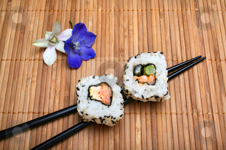 Sushi stock photo, Two pieces of sushi resting on chopsticks on bamboo mat with flower garnish. by Clay Anthony