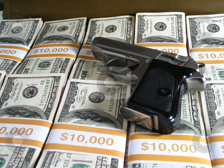 Cash stock photo, Small semi-automatic handgun sitting on bundles of $100 bills. by Clay Anthony
