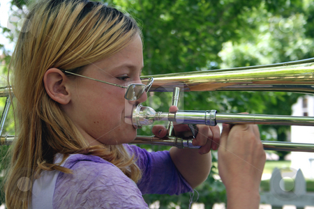 Natural trombonist stock photo, Pre-teen girl playing a trombone outside. by Clay Anthony
