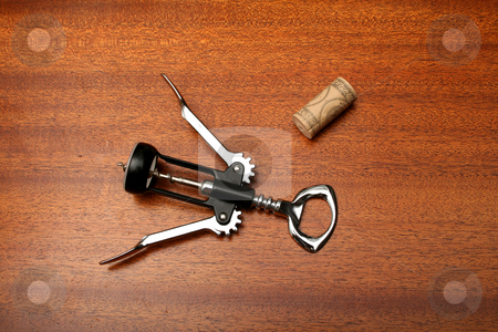 Corkscrew stock photo, A wine opener and cork sitting on wooden bar surface. by Clay Anthony