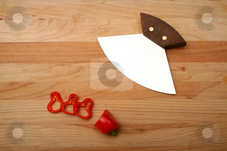 Ulu stock photo, An ulu (Eskimo) knife sitting on a cutting board next to chopped red pepper. by Clay Anthony