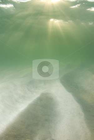 Underwater Beach Sun rays stock photo, A view of the rippled ocean floor, the action on the surface, and the sky and golden sunset rays breaking through the water. Double top sunrays. by A Cotton Photo