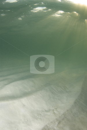 Underwater Beach Sun rays Top Corner stock photo, A view of the rippled ocean floor, the action on the surface, and the sky and golden sunset rays breaking through the water.  Sunrays positioned in top corner. by A Cotton Photo