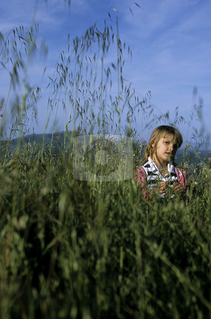 Girl in Grass stock photo, Young girl in a field of tall grass under a blue sky with hills in the background. by A Cotton Photo