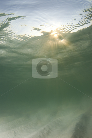 Underwater Beach Sunrays Top Third stock photo, A view of the rippled ocean floor, the action on the surface, and the sky and golden sunset rays breaking through the water.  Sunrays in top third. by A Cotton Photo