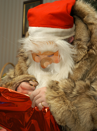 Santa claus stock photo, Santa Claus using a magnifier to see the namen on the christmas present by Johan Lenell