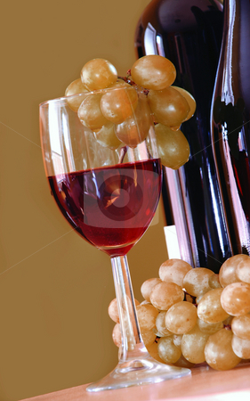 Red wine with grape bunch stock photo, Red wine glass with grape and bottle over green by Julija Sapic
