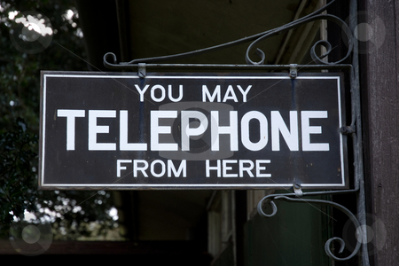 Telephone Here stock photo, Old telephone sign in black attached to an old office by Paul Phillips