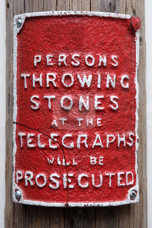 No throwing stock photo, Red sign attatched to a telegraph pole warning not to through stones at the pole by Paul Phillips