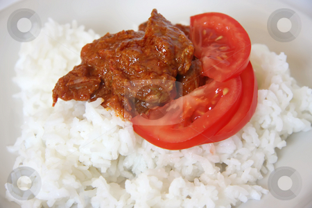 Curry and rice stock photo, Spicy meat curry with red gravy on rice with sliced tomatoes by Kheng Guan Toh