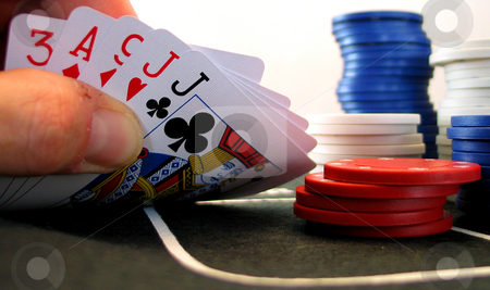 Poker Cam stock photo, Table-top view of hand holding poker hand being peeked at on felt table top with red, white and blue poker chips in the background. by Clay Anthony