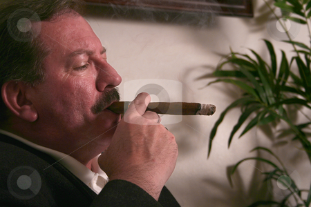 Puffing Away stock photo, Mike Walsh enjoys a cigar while relaxing in his Casper, WY apartment. by Clay Anthony