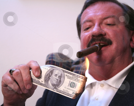 Money to Burn stock photo, Mike Walsh lights a cigar with a $100 bill in his Casper, WY apartment. by Clay Anthony