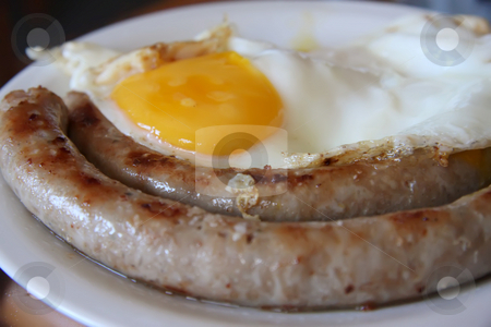 Sausage and eggs stock photo, Breakfast sausages and fried eggs on white plate by Kheng Guan Toh