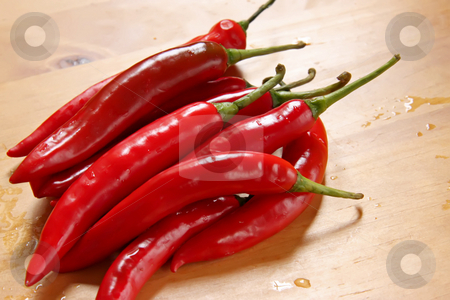 Fresh chillis stock photo, Fresh whole red chillis on chopping board by Kheng Guan Toh