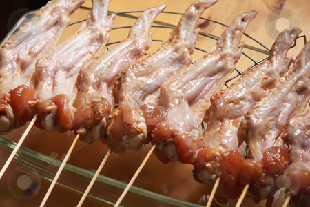 Raw chicken wings stock photo, Raw chicken wings marinating on wooden skewers by Kheng Guan Toh