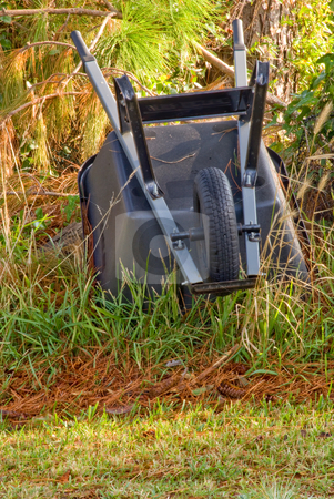 Wheel Barrow stock photo, A wheel barrow stored beside a tree. by Robert Byron