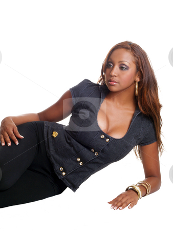 Woman reclining stock photo, Young mixed black woman reclining on floor in pants by Jeff Cleveland