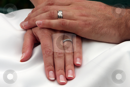 Together stock photo, Bride and Groom's hands clasping each other against a white wedding dress. by Megan Lorenz