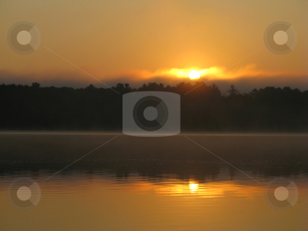 Sunrise over calm lake stock photo, The dawn sun peeks over the Minnesota north woods onto the calm waters of Cutfoot Sioux Lake in this serene setting by Bruce Peterson