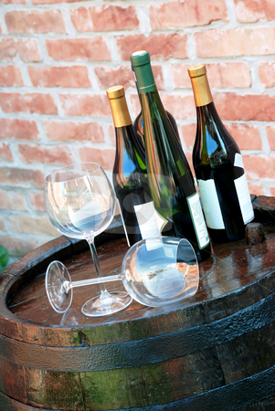 Wine over wood barrel stock photo, Glasses and bottles of wine lying over wooden barrel by Julija Sapic