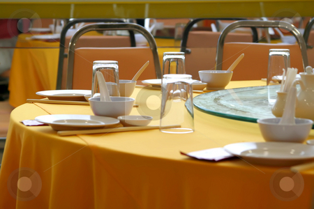 Chinese restaurant table stock photo, Place settings in a chinese restaurant table with yellow cloth and white porcelein by Kheng Guan Toh