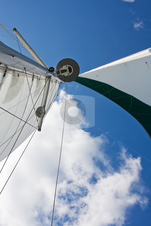 Sails stock photo, Sails, GPS and radar of a catamaran boat with a deep blue sky and white cloud by Paul Hakimata