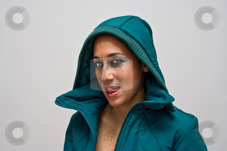 Sexy girl licking lips stock photo, A sexy young woman licking her lips, wearing a green winter coat zipped open and the hood covering her head, isolated on white by Paul Hakimata