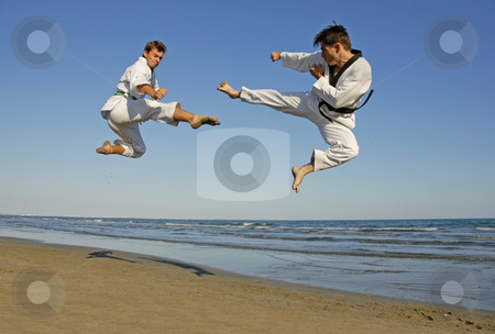 Taekwondo on the beach stock photo, Training of the two young men on the beach: taekwondo, martial sport by Bonzami Emmanuelle