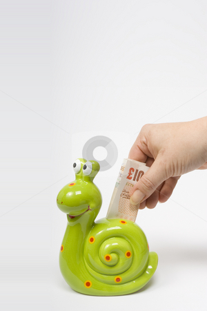 Saving Money stock photo, A female hand deposits a UK ??10 banknote into a green, snail shaped money box symbolising slow sure progress in investment. by Steve Smith