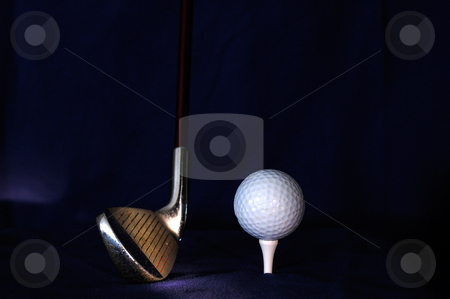 Stock Photo of a Golf Club and Ball stock photo, A young child's well used iron still has plenty of hits left in it. by Tim Thompson