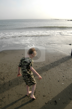 Ocean 2 stock photo, As the evening sun casts shadows on the beach, this boy digs in the sand with his toes as he puts off having to go home as long as possible. He was spending the day on the beach near Ocean Shores, Wash., with his family. by Tim Thompson