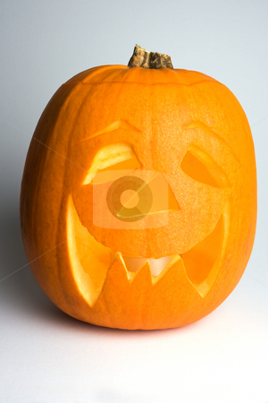 Lighted Halloween Pumpkin stock photo, A lighted halloween 'Jack'o'Lantern' pumpkin against a white background with left-hand side in partial shadow. by Steve Smith