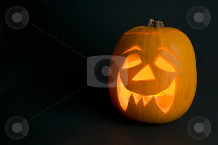Lighted Halloween Pumpkin stock photo, A lighted halloween 'Jack'o'Lantern' pumpkin on the right-hand side of a dark frame with some light spill in the foreground. by Steve Smith