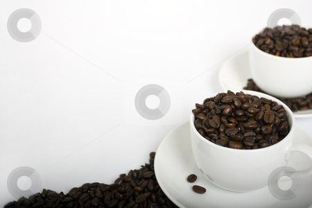 Coffee Cups with Coffee Beans stock photo, Two coffee cups on the right-hand side of a white background filled with attractive coffee beans. Coffee beans placed around saucers and alog bottom of the frame. by Steve Smith