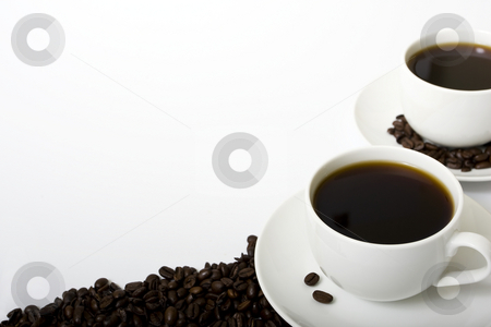 Coffee with Coffee Beans stock photo, Two coffee cups on the right-hand side of a white background filled with coffee. Coffee beans placed around saucers and along bottom of the frame. by Steve Smith