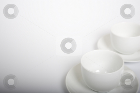 Coffee Cups stock photo, Two coffee cups on the right-hand side of a white background. Gradient light drop off in the bottom of the frame. by Steve Smith