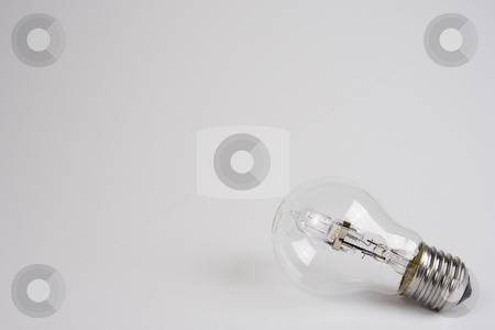 Halogen Lightbulb stock photo, A halogen lightbulb laying on it's side on the right-hand side of a white frame. by Steve Smith