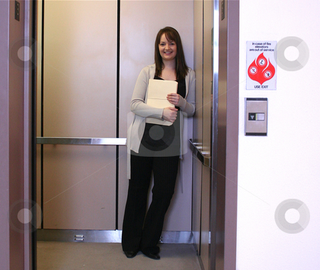 Megan elevator (horz) stock photo, Female office worker on elevator. by Clay Anthony