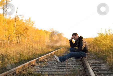 Contemplation stock photo, A man sitting on the railroad tracks, sitting in a deep depression by Richard Nelson