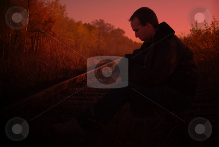 Dark Mood stock photo, Depressed man sitting on train tracks, perfect for a dark mood by Richard Nelson