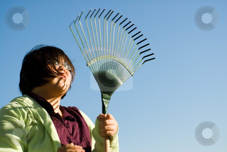 Raking Leaves stock photo, Low angle view of a young girl holding a rake by Richard Nelson