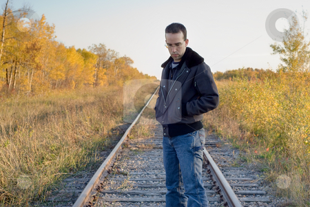 Depression stock photo, A young man standing by some train tracks looking depressed by Richard Nelson