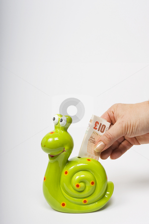 Snail Savings stock photo, A female hand deposits a UK ??10 banknote into a green, snail shaped money box symbolising slow sure progress in investment. by Steve Smith