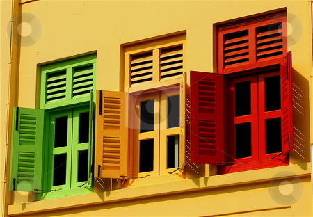 Colourful Windows stock photo, A set of three shutters against a yellow background by Jeff Crowe