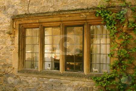 Window in a stone house stock photo, A stone house in the Cotswolds, England, looking in through the window to the cottage by Jeff Crowe